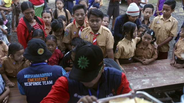 The Latest Evacuees get meals at temporary camps on Bali
