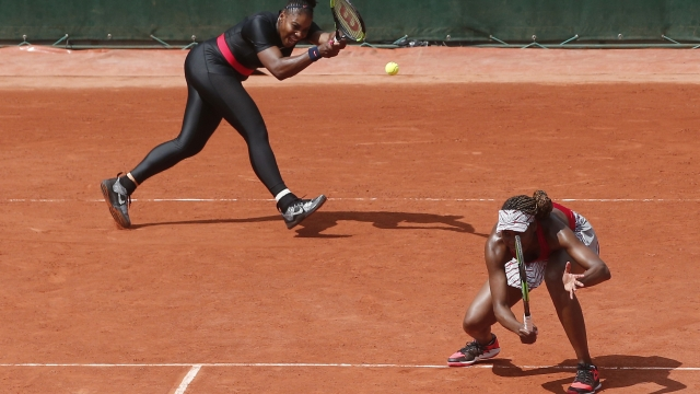 The Latest: Williams sisters win in return to Slam doubles